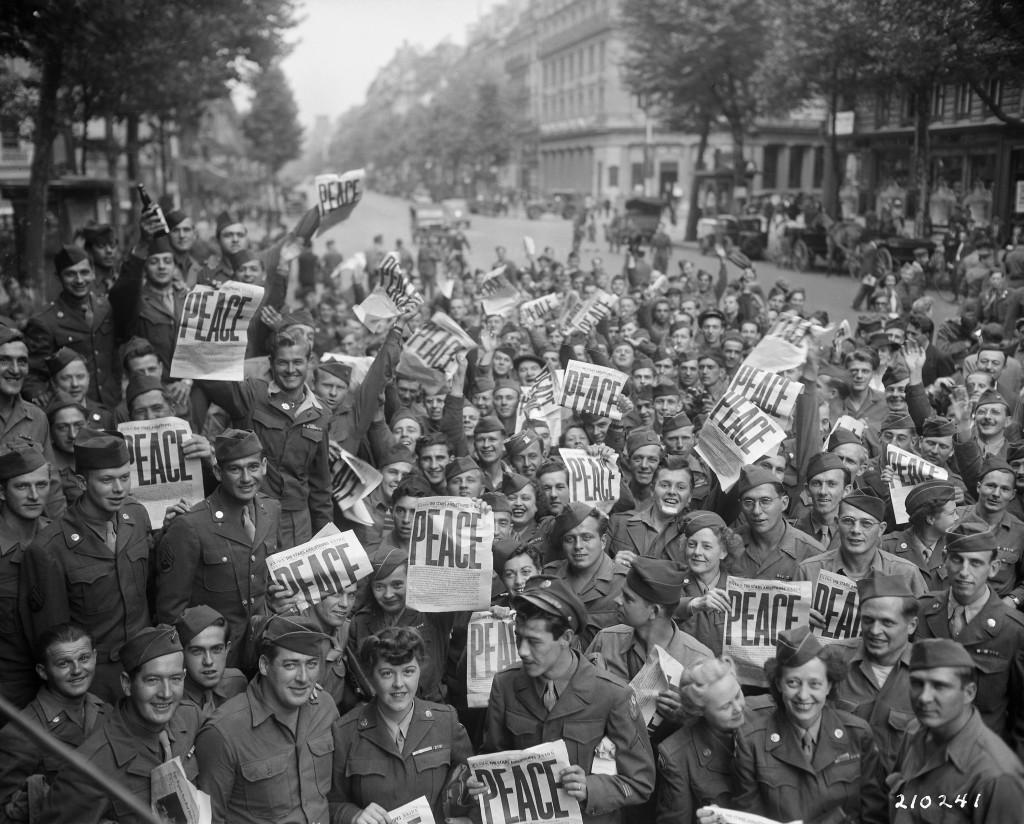 Příslušníci a příslušnice americké armády oslavují před pařížským klubem Amerického červeného kříže zprávu o japonské kapitulaci. Paříž, 15. srpna 1945. (Zdroj: U.S. National Archives)